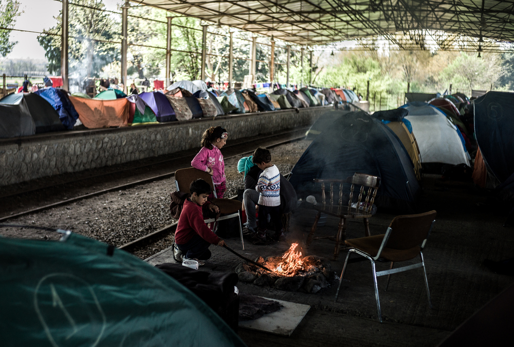 A mother and her three children by the fire in a train depot in Idomeni. They are waiting for the border to open with Greece and Macedonia so they can continue their journey to Western Europe.