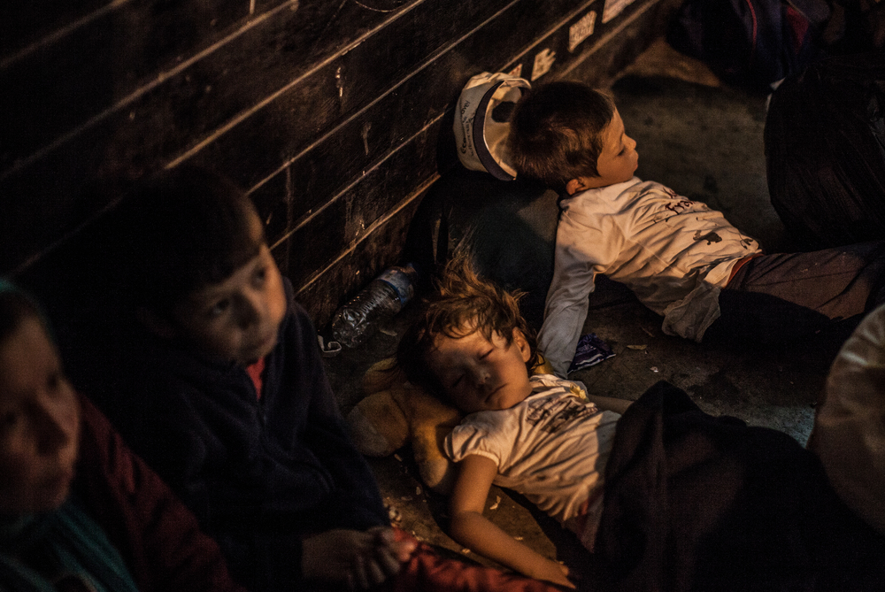 A mother from Afghanistan sits as her three children sleep on the side of a street in Athens, Greece. They are waiting for a bus that is going to take them to the border with Macedonia.