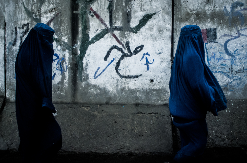 Two women walk past the bomb proof concrete walls guardian the American Embassy in Kabul, Afghanistan.