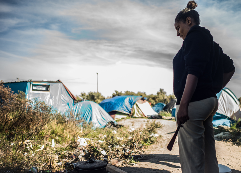 Daniat from Eritrea prepares lunch in the Calais Refugee Camp known as the Jungle. She camps here, and during the night goes to try and board trucks that are bound for the UK.
