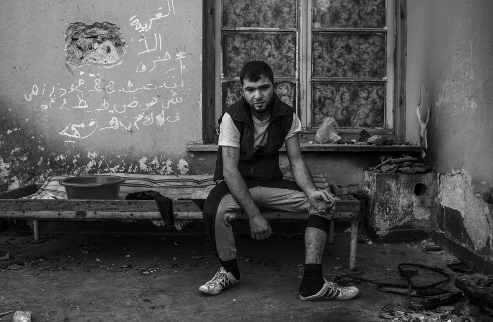 Mohamed from Raqqa in Syria, sits on the roof of Idomeni train station showing a bullet wound he got after being shot by an Islamic State militant.  Idomeni, Greece  April 2016