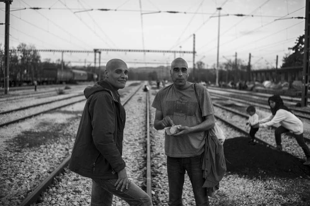 Karim (left) and Hassan (right) from Algeria, standing in the centre of the tracks outside Idomeni Station. An outbreak of lice in the camp means many of the residents have shave their heads.  Idomeni, Greece  April 2016