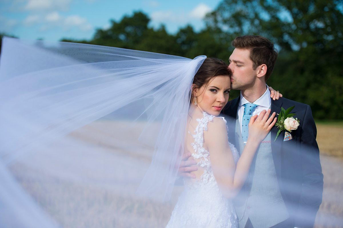 photograph of a bride a groom in stubble field with veil blowing in the breeze