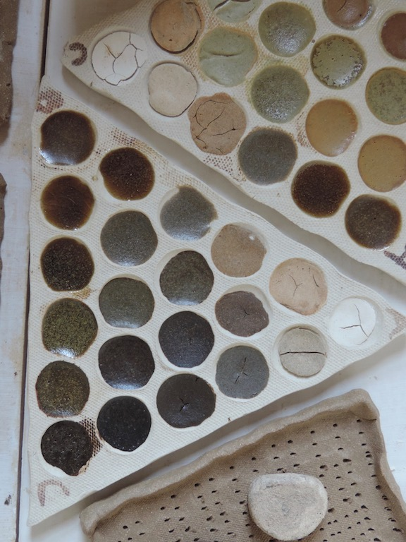 Triaxial blend tests fired to 2250 f. in oxidation. Lower left tile shows promising results for a diverse range of glazes using slate powder, refractory kaolin, and silty clay soil collected in a marble quarry