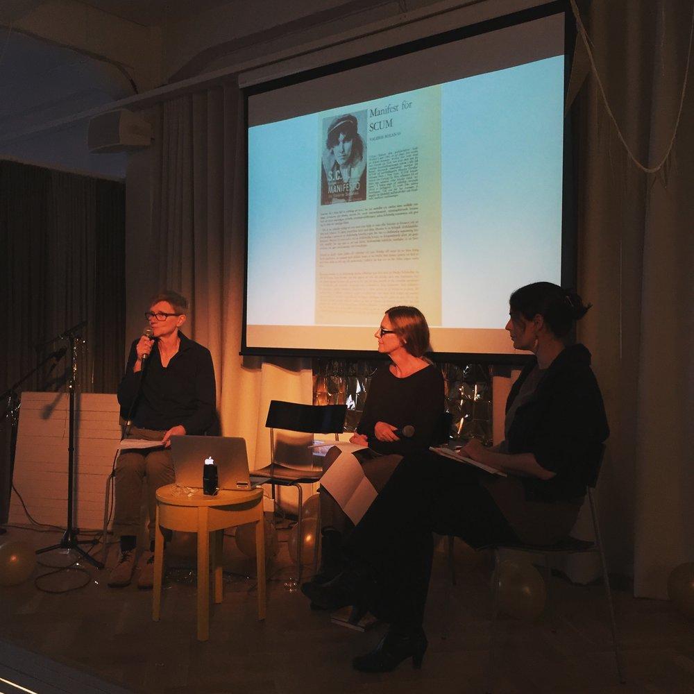 Annika Ruth Persson, Linda Östergaard och Patricia Lorenzoni, med Lars Bäckströms översättning av Valerie Solanas SCUM-manifest ur Ord&Bild 1969 i bakgrunden.