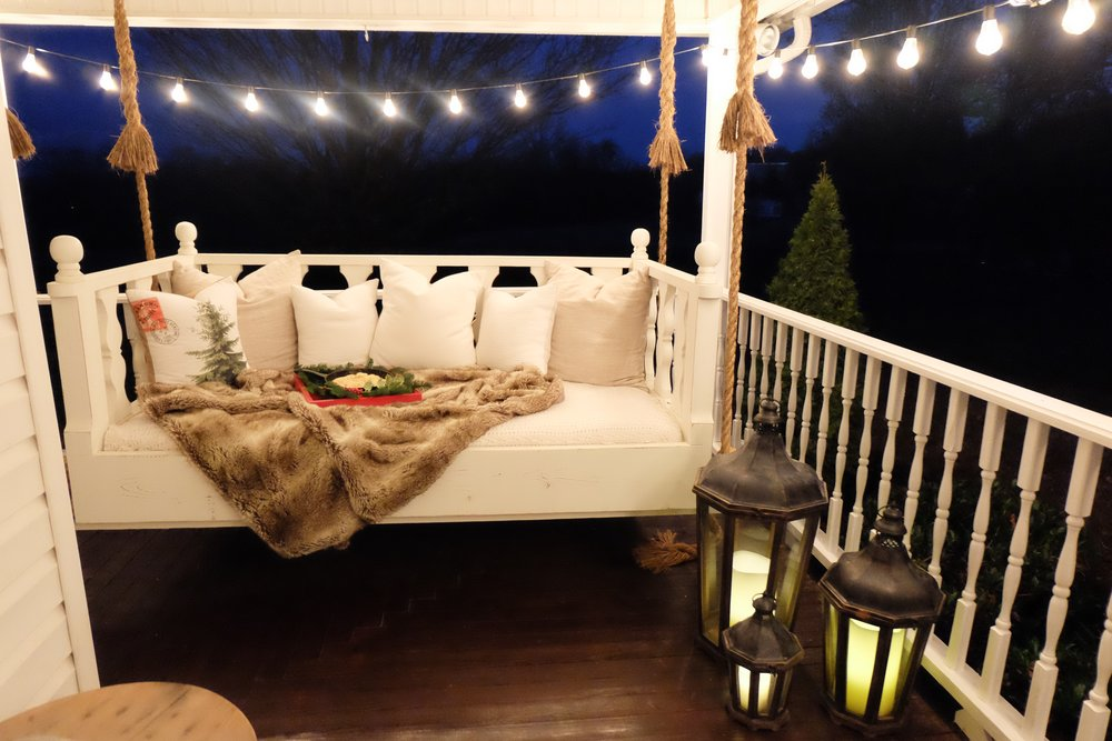 Our swingbed is always a huge hit for guests. We got it at Hammmadefurniture, the faux fur throw and candles are from Grandinroad, pillows are from Joliemarche and the lanterns are Pottery Barn!  I love decorating the swing for every season!! it really is so comfy!
