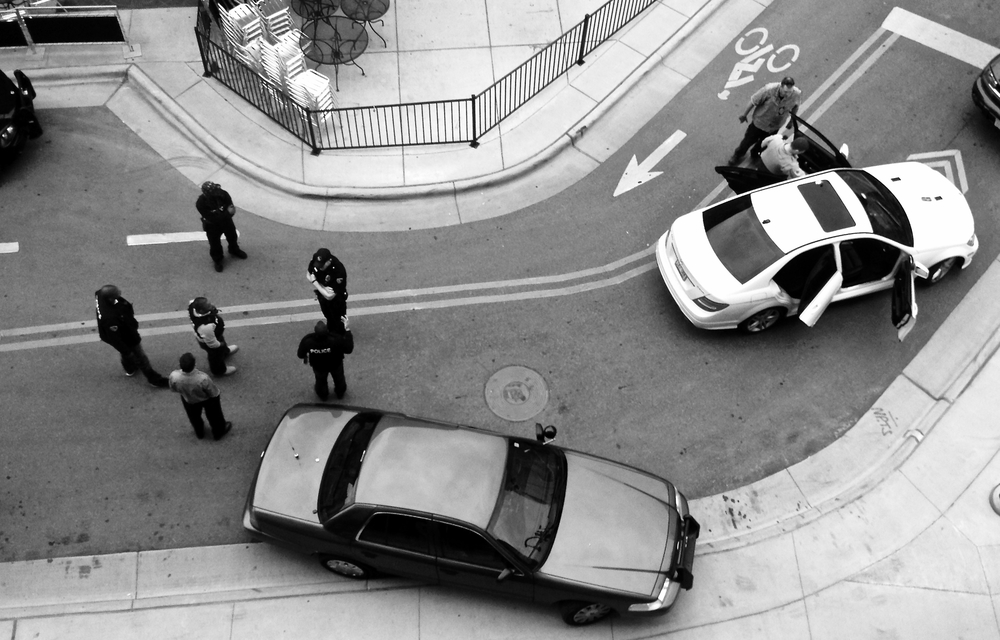 Scene of the Crime (1). Downtown. Madison, Wisconsin. April 2016. Police talk and gather evidence at the scene of an armed traffic stop and arrest.  © William D. Walker