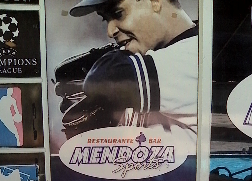 Photos of Ramiro Mendoza, the owner's brother, hang on the wall of the Mendoza restaurant.