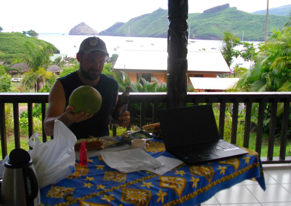 Justin considers his feast of pomplemous, and a baguette and mackerel sandwich served on the porch of the pension where the crew stayed for the second part of their stop in Nuku HIva.