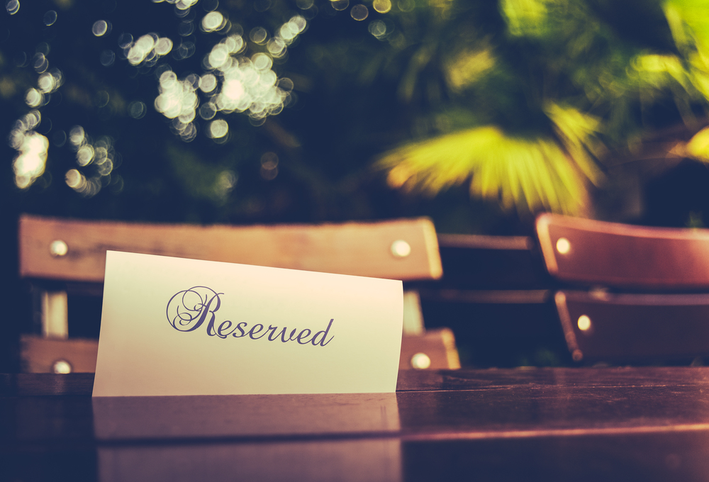 reserved-sign-on-wooden-dinner-table-trees-in-background.jpg