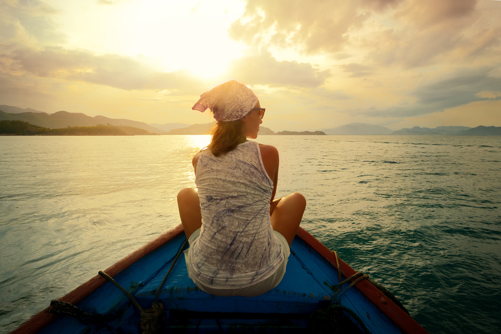 woman-traveling-by-boat-at-sunset-among-the-islands.jpg