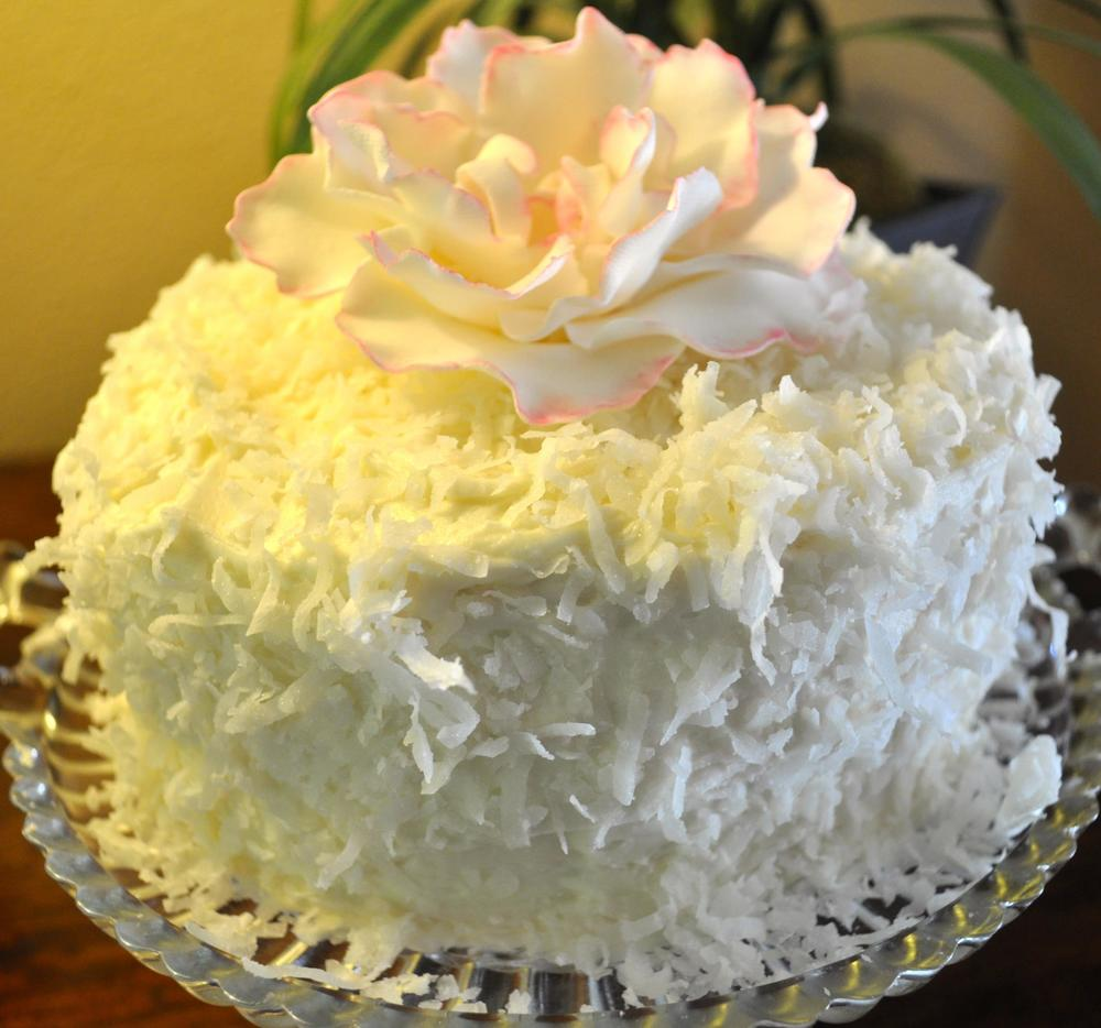 "Dreamy Coconut Cake frosted with an Old Fashioned Boiled Icing, garnished with coconut.  8"" 3-layer cake: Serves 15    $50  Sugar Peony $20"
