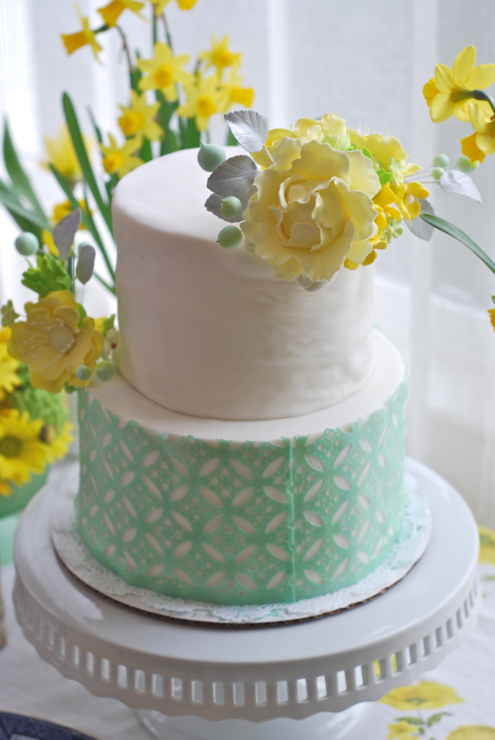 Fondant covered cake with sugar flowers and decorative, edible wafer paper bottom tier.