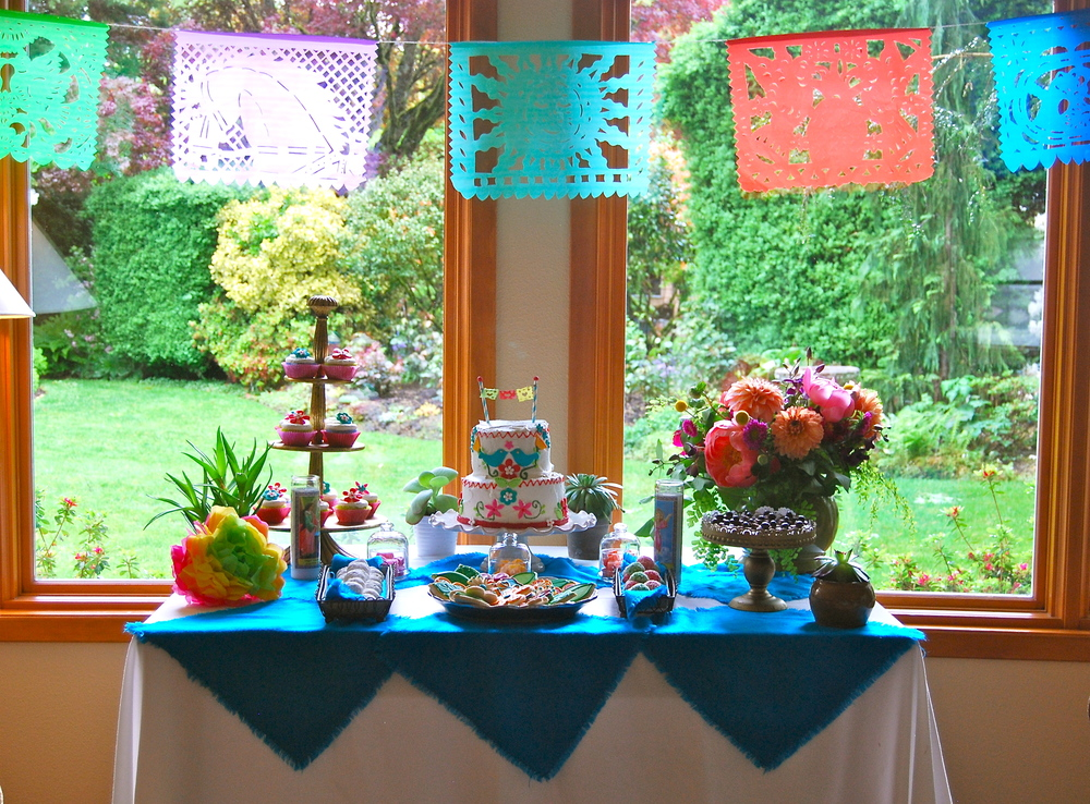 Dessert Buffet featuring a raspberry filled cake, cupcakes, decorated sugar cookies, coconut macaroons, mexican tea cakes, chocolate cheesecake brownie bites, and homemade gumdrops.