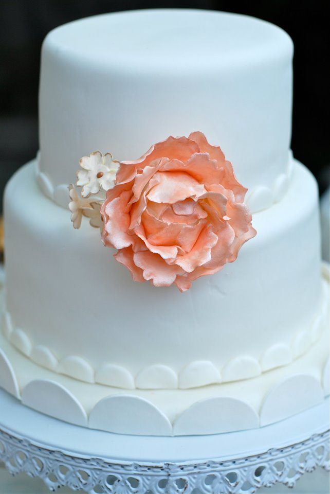 Two-tier fondant covered banana cake adorned with a delicate handmade sugar peony