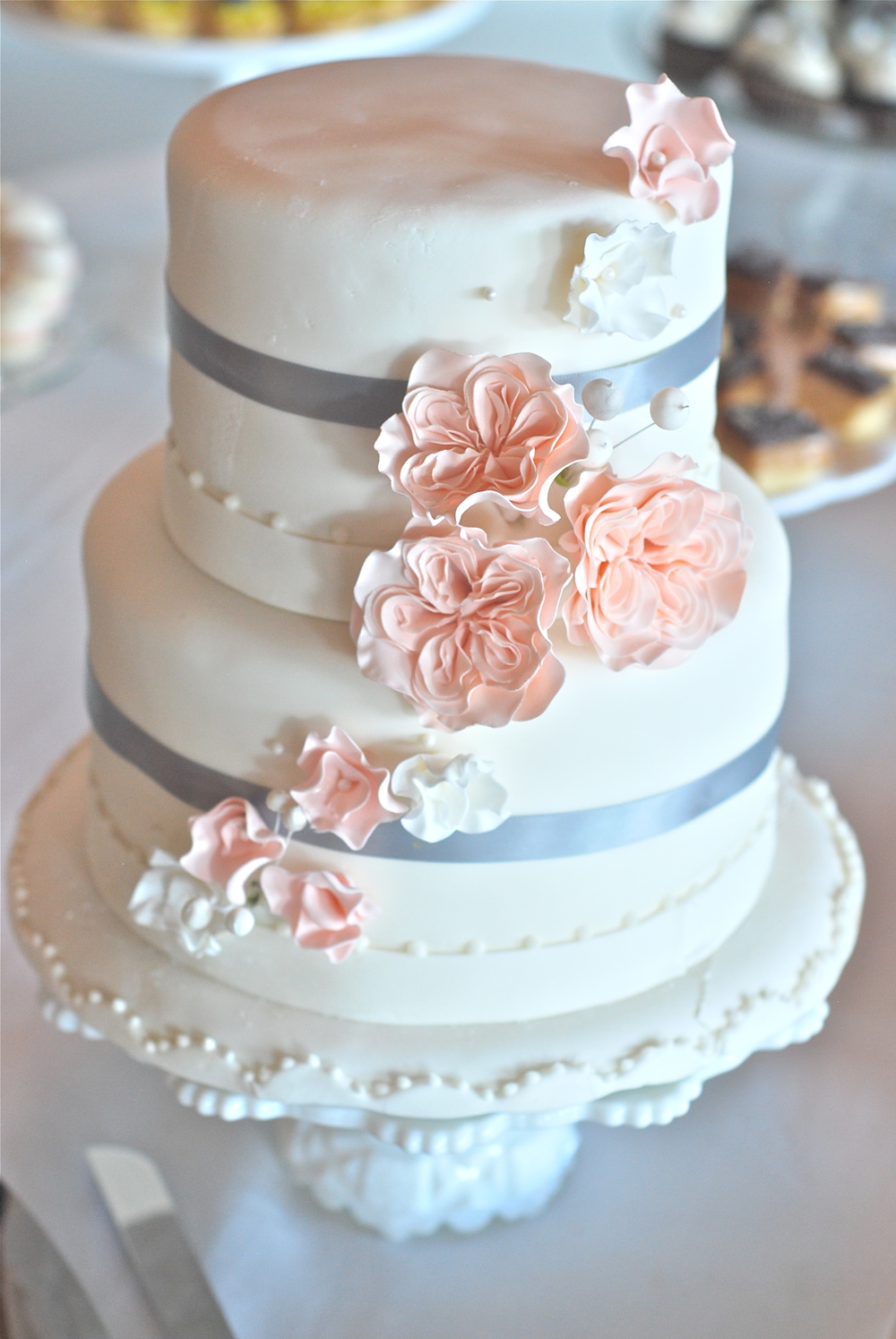 Two-tier fondant covered carrot cake, decorated with handmade sugar flowers.
