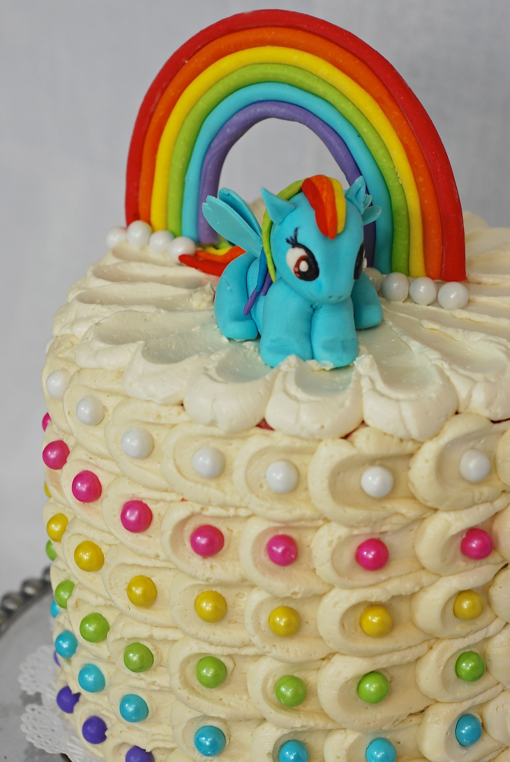 Rainbow Sixlet covered Sweet Vanilla Cake.  Inside, each layer is a different color of the rainbow!