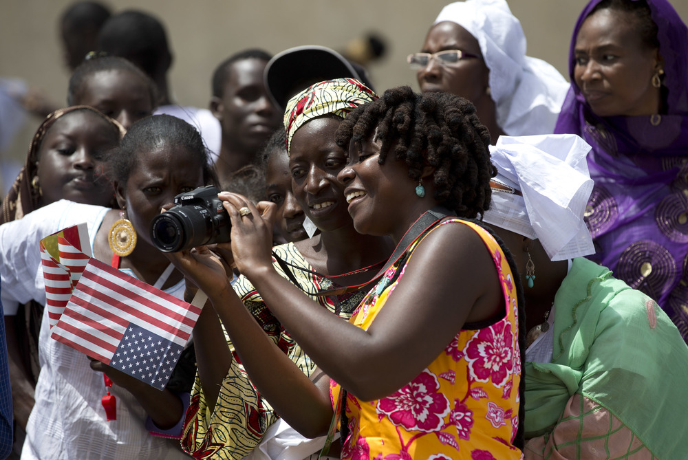 Here, I am showing Senegalese women pictures of First Lady Michelle Obama. (Credit: Carolyn Kasper/AP)