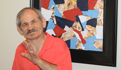David poses next to one of his framed collage pieces he makes using scraps of ripped paper.