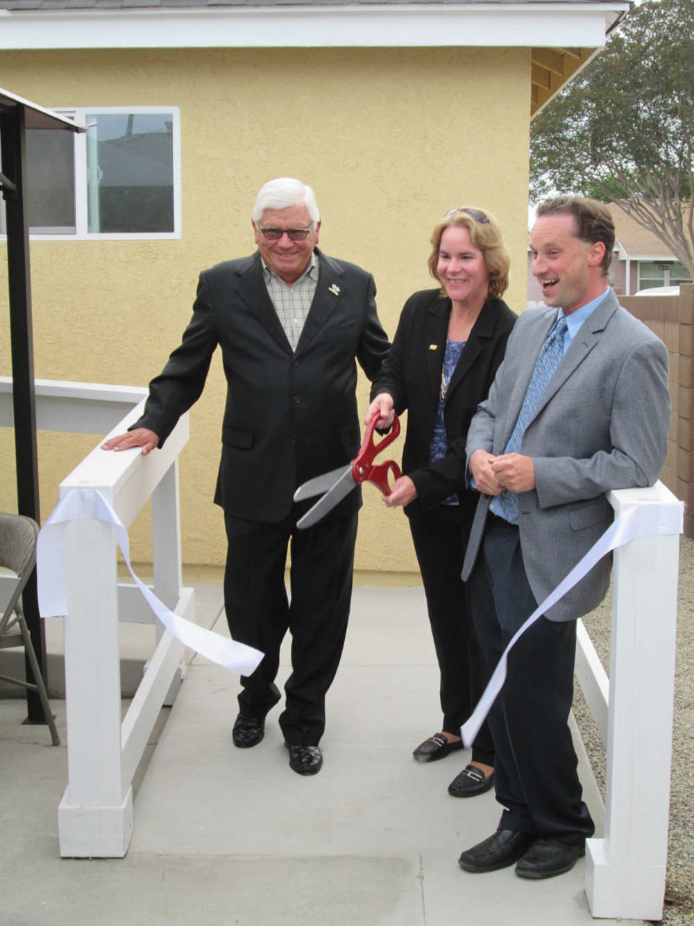 From left: Board Member Phil Appleby, Norwalk Housing Manager Kristin Maithonis, and HOPE Executive Director Kristin Martin cut the ceremonial ribbon to welcome  the completion of a new home.
