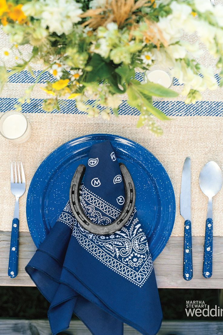 The rehearsal dinner tables were set in true rustic country style with lanterns, flowers, and horseshoes holding in place these bandana's/napkin's with the couples monogram incorporated into the design.