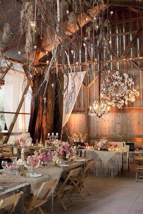 A barn decorated with mixed flowers, hanging lanterns and a chandelier. Beautiful rustic perfection!