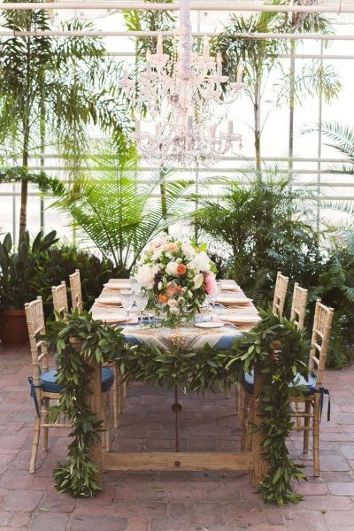 Gold Tiffany chairs, floral runner on the table ends and surrounded by leafy green palms.