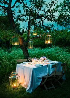 A romantic dinner for two under the night sky - over head lighting hung from trees & surrounded by candlelit lanterns.