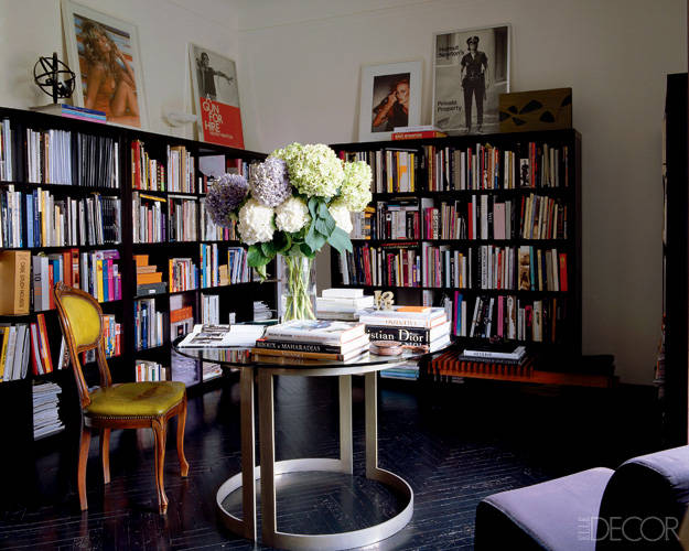 In the studio's library, vintage posters and a Chris von Wangenheim photograph are propped on ebony bookcases, and the table is a 1970s Piero Pinto design.