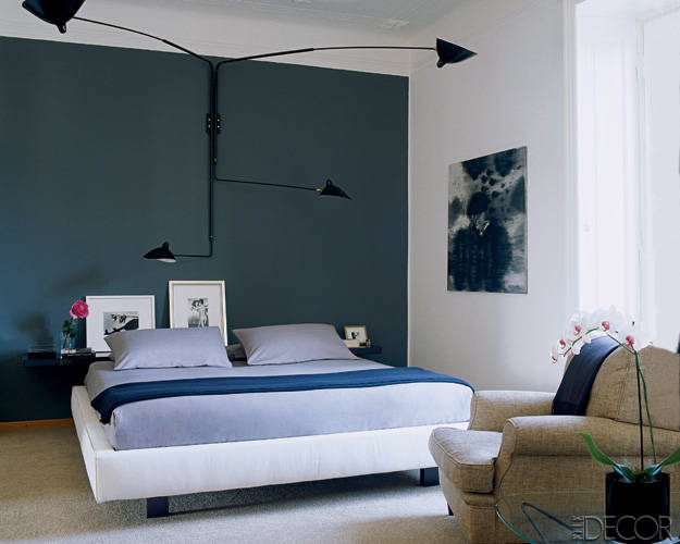 In the master bedroom, a Serge Mouille light fixture is suspended over a bed dressed in linens by Nate Berkus for HSN