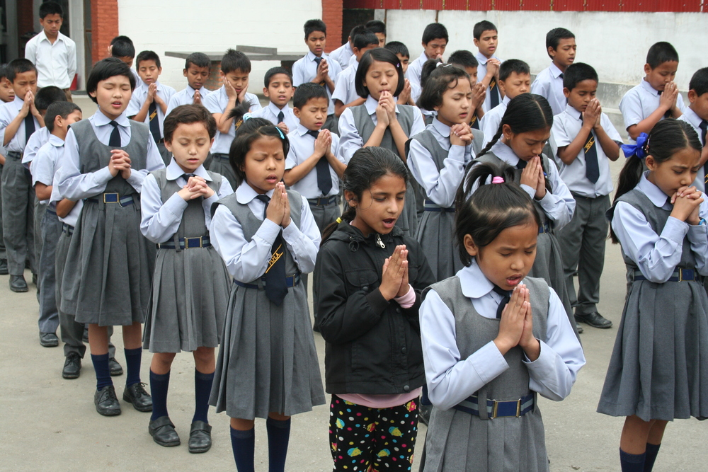 Children praying at our school, Mercy Mission Academy, to start the day