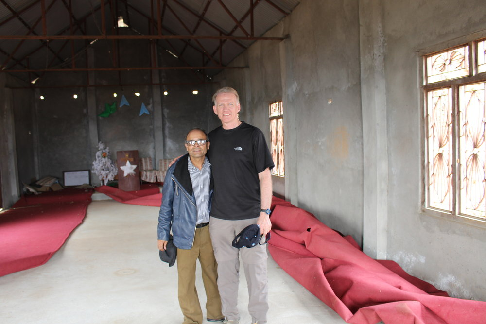 The village pastor, the donor of the land, with Joel, inside the village church.