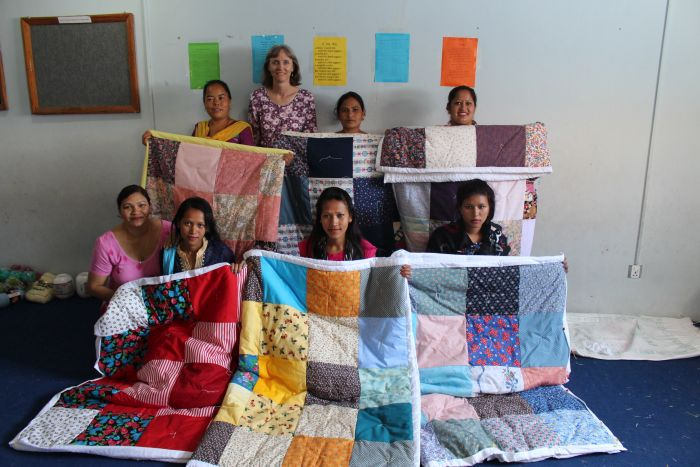 The women learning how to quilt