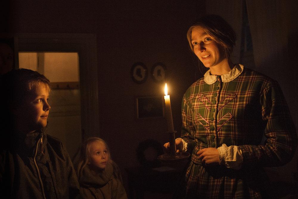 Dagene bliver kortere, men med det elektriske lys har vi kunnet gøre dagene lidt lysere. Sådan var det ikke i 1800-tallet. Da blev det rigtig mørkt. Skumringen er for alvor i gang i den lavloftede stue, hvor lugten af brændt træ fra ovnen breder sig. Indenfor står Maren Jensen og byder velkommen i præstehusets fine stue, som er bygget efter 1800-tallets standard. Maren Jensen hedder i virkeligheden Thilde Maj Holgersen, men to gange om ugen er hun aktør og holder mørkningstid i præsteboligen i Den Gamle By i Aarhus. Oplyst af et stearinlys, et spejl og en lysedug går fortællingerne om livet i 1800-tallet i gang.