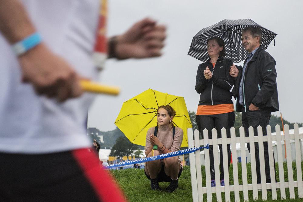 Kommentatorens stemme spreder sig i Mindeparken, hvor der i disse dage står telte fra diverse firmaer, da der på 35. år afholdes den årlige DHL-stafet. Jane Fuglsang var anden løber for sin virksomhed, hvor hun til daglig arbejder som sælger. Nu står hun i regnen med sin kæreste, Morten Østergård, og datter, Nina Fuglsang, og venter på de sidste holdkammerater. Jane Fuglsang løb sin runde på 29,56 minutter, og som hendes kæreste pointerer, er det vigtigt med de sidste decimaler, der viser, at hun kan løbe distancen på under 30 minutter. 47.000 motionister ventes at deltage i stafetten over tre dage.