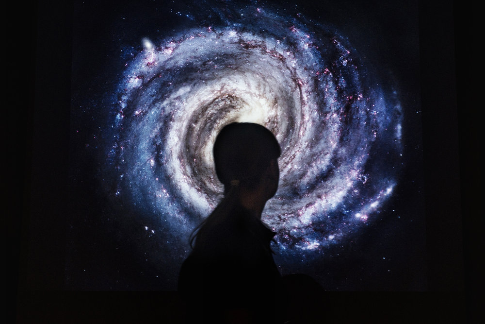 """Der bliver ikke sparet på """"Star Wars""""-referencerne i Julie Gadebergs forevisning i Ole Rømer-Observatoriet på toppen af Aarhus. Selv om der ligger en tyk dyne af skyer hen over nattehimlen, går gæsterne ikke uoplyste fra arrangementet. »Hvad mangler på himlen?« spørger Julie Gadeberg, mens hun trækker en tavle med et landskab uden noget på himlen frem. »Stjerner,« siger en af de ca. 20 fremmødte gæster. Derfra fortsætter aftenen gennem hele solsystemet og endnu længere væk."""