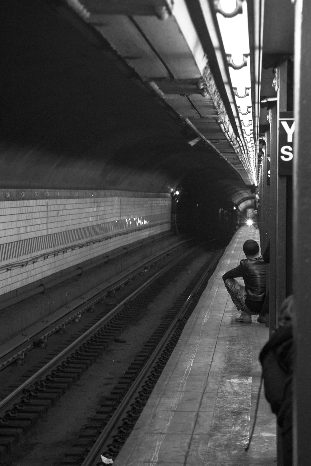 A young man waits for the F train at the York St. station, the last stop on the line before going into Manhattan from Brooklyn (or, the first stop in Brooklyn after leaving Manhattan)
