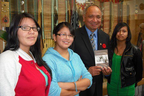 Reanne Elkins, Taylor Myers and Larissa Myers present Lieutenant Governor Stephen Pointe with a copy of the Squaw Hall Project DVD.