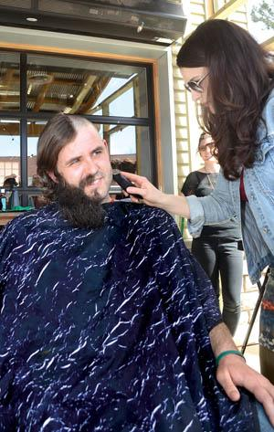 Aaron Darling gets the left half of his beard and hair shaved off by Maggie Martin of MAK Salon & Spa during the April 15 Shears & Beers Fund-Razor at the Greenbush Brewing Annex in downtown Sawyer. - photo by David Johnson