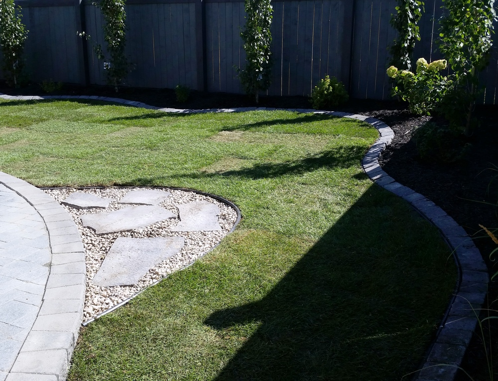 Backyard Cobble Patio With Flagstone Extension And Brick
