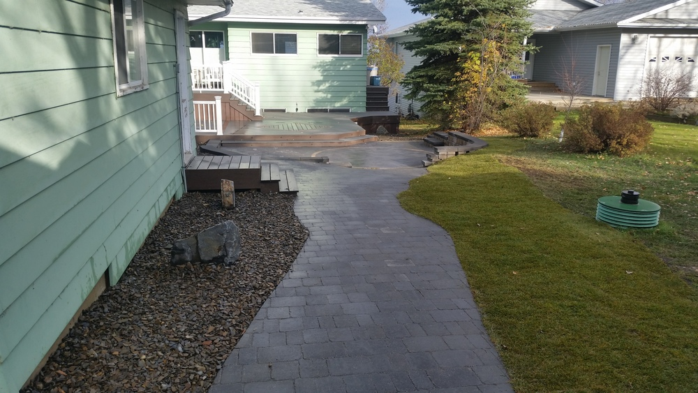 Walkway from driveway to patio with new rockbeds beside garage.