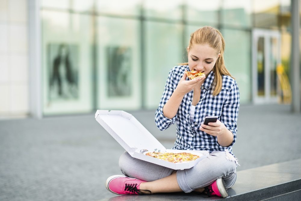 iStock_Girl Eating Pizza Looking at Cell.jpg