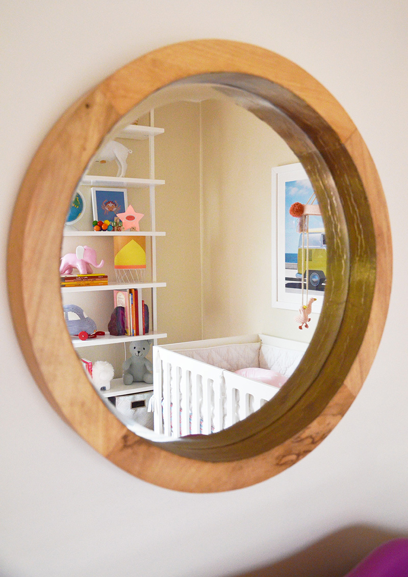 A round wooden mirror was chosen to bring a warm,natural element to this peaceful nursery