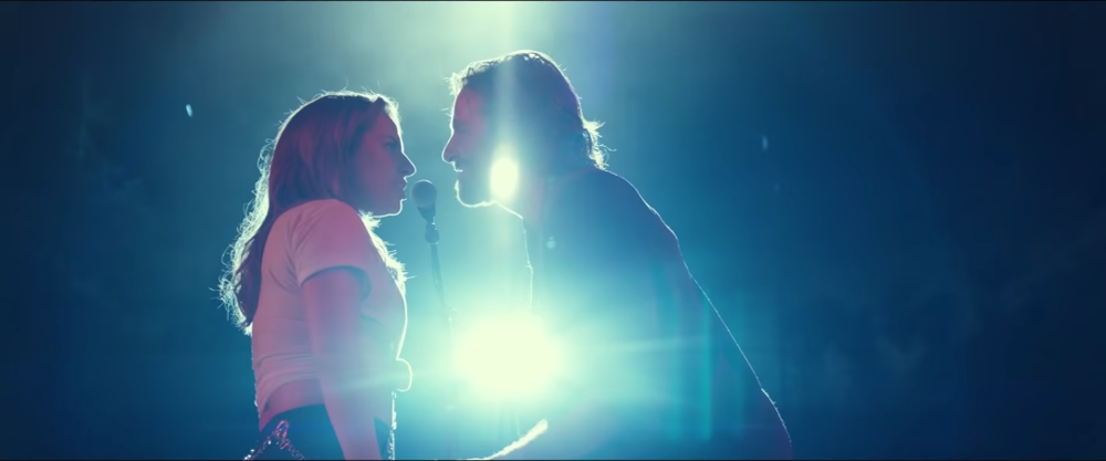 A frame of Bradley Cooper's character, Jack, and Lady Gaga's character, Ally, performing their first song together, Shallow.