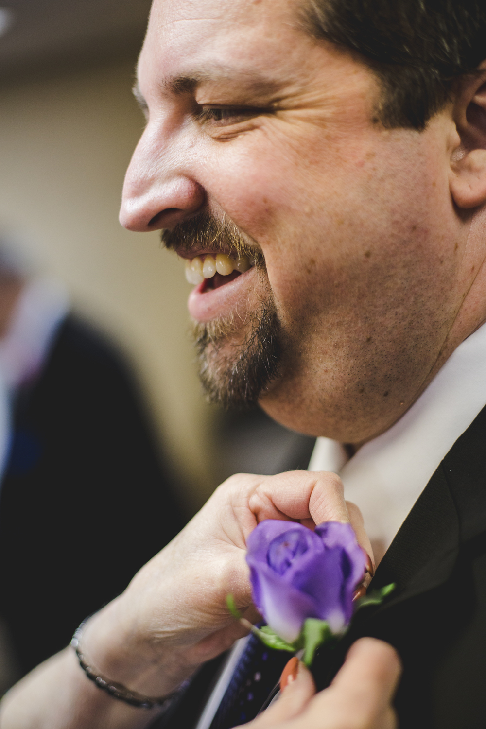 rs russell groom puts boutonnière on smiling