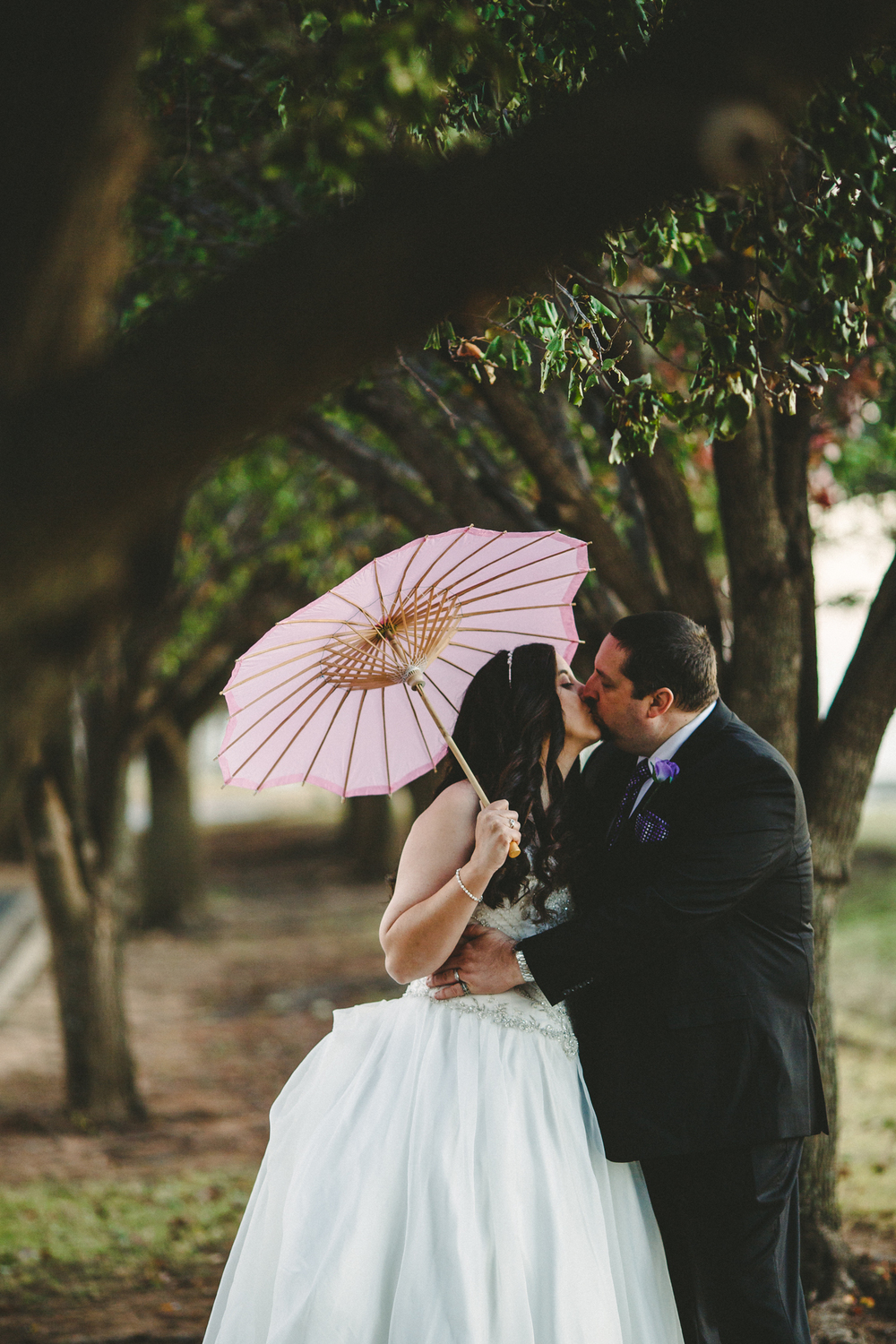 rs groom kisses bride under greenery trees oklahoma city