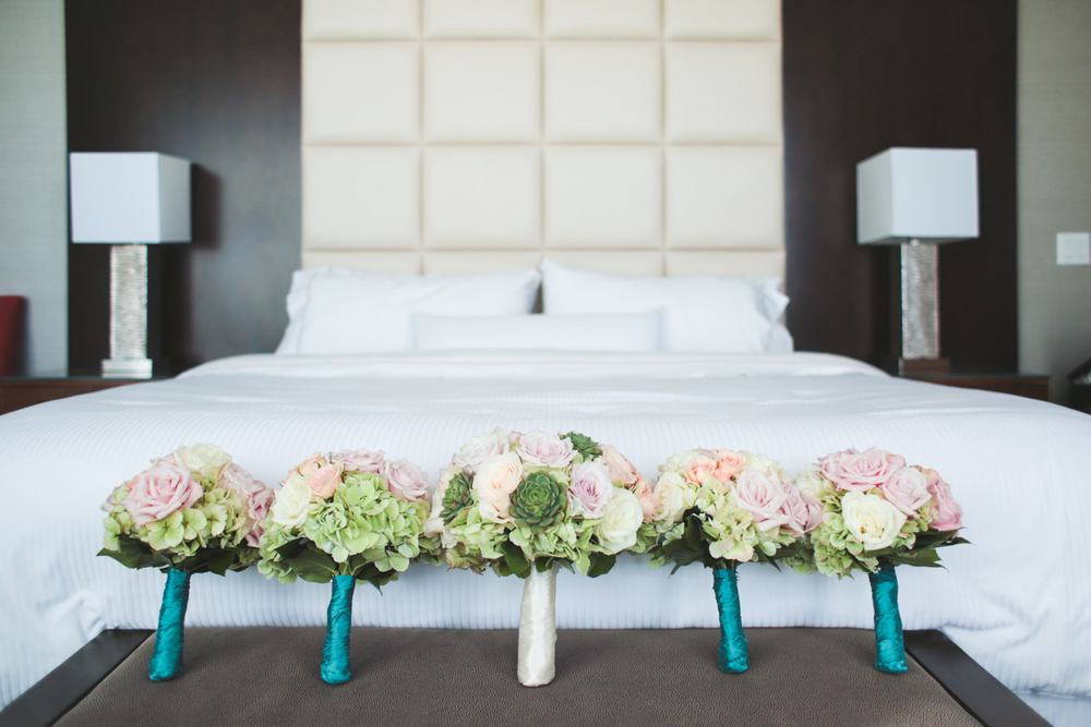 bridal bouquets and flowers lying against bed hj