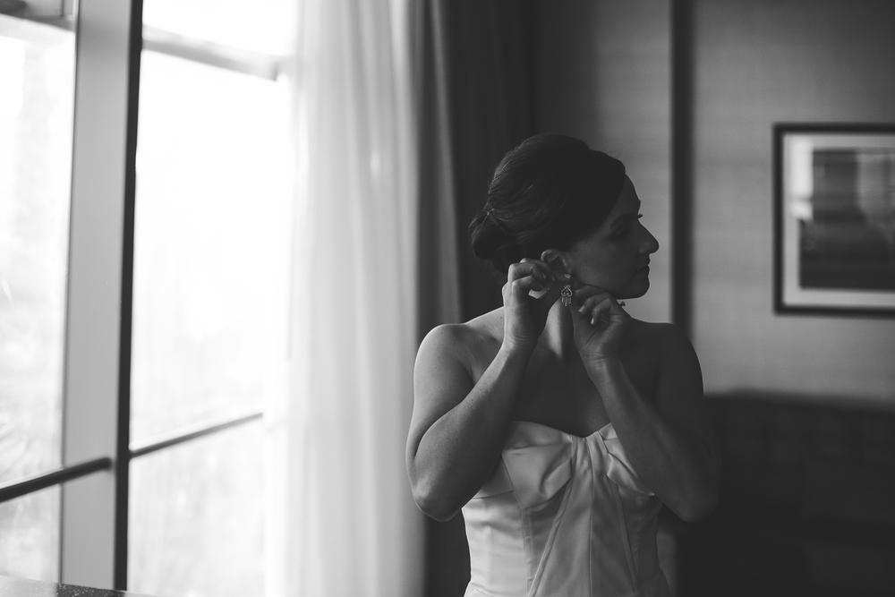black and white bride putting on earrings hj