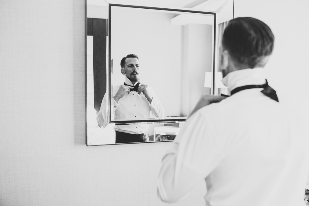 groom putting on bow tie black and white hj