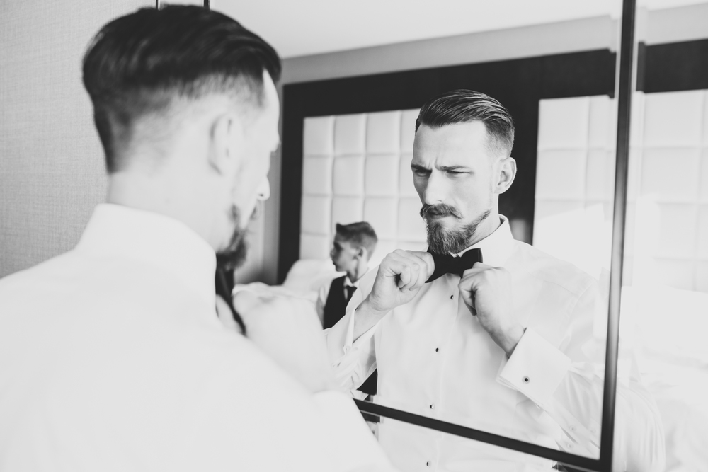 groom finishes his bow tie black and white hj